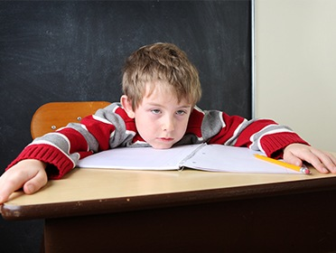 Young boy falling asleep in class
