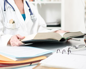 Medical professional with books and paperwork